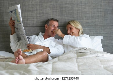 Couple in bathrobes relaxing on bed in hotel bedroom reading newspaper and eating continental breakfast