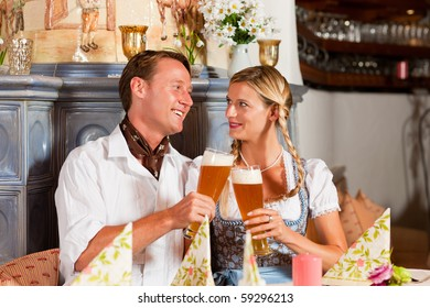 Couple in Bavarian Tracht drinking wheat beer in a typical pub, clinking classes