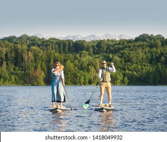 Couple in bavarian traditional dresses stand up paddling on a lake