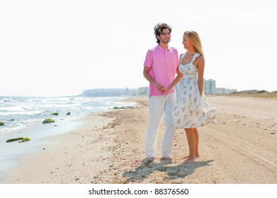 Couple at the beach holding hands and walking. Sunny day, bright colors. Europe, Spain, Costa Blanca