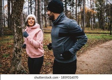 Couple with beanie and gloves running in woods at autumn and recreating, Healthy life concept.
