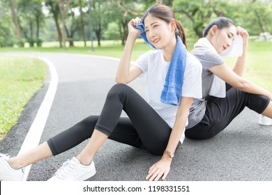 couple beautiful asian female exercise in public park, they absorb sweat with her towel, they relax and smile on nature background, health promotion