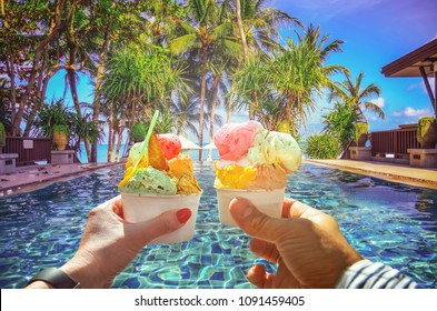 Couple with beautiful bright  sweet Italian ice-cream with different flavors  in the hands  . Background of  panoramic view of tropical beach with coconut palm trees. Koh Samui, Thailand