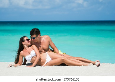 Couple of beautiful woman and man are lying on the white sand of caribbean coastline at summer sunny day