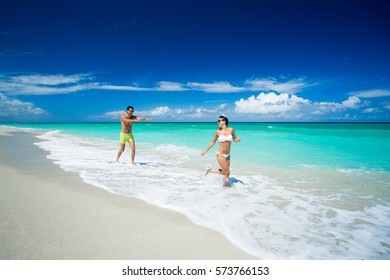 Couple of beautiful woman and man are running on the beach of caribbean sea at summer sunny day