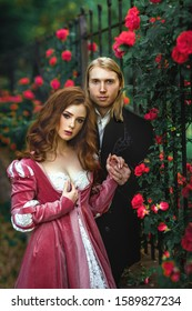 A couple of a beautiful young people posing in vintage medieval dresses on a nature background with roses. Love story.