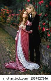 Ein paar schöne junge Leute, die sich in alten mittelalterlichen Kleider auf Naturhintergrund mit Rosen posieren. Liebesgeschichte.