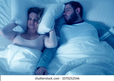 Couple in bed, man snoring and woman can't sleep, covering ears with pillow for snore noise