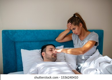 Couple in bed, man snoring and woman can't sleep. Snoring man and young woman. Couple sleeping in bed. Young girl can't sleep because of her man's snoring. Snoring man problem