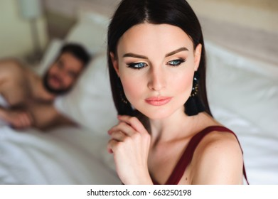 Couple in bed, portrait of a sad woman in bed with her husband