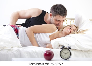 Couple in Bed - smiling man embracing happy woman
