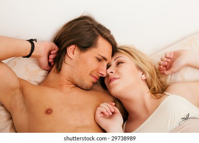 Couple in bed waking up together, he is stretching