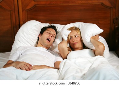 Couple in bed while the woman is trying to sleep and the man is snoring