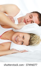 Couple in bed. Woman trying to sleep while a man is snoring