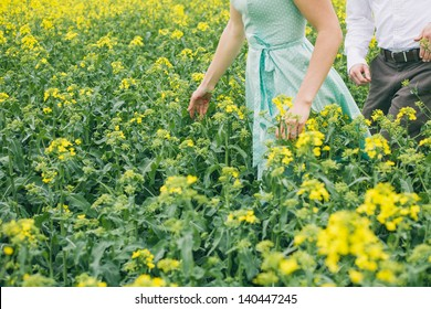 Couple before wedding running in colza field, girl with turquoise dress, without face, vintage color, engagement photo