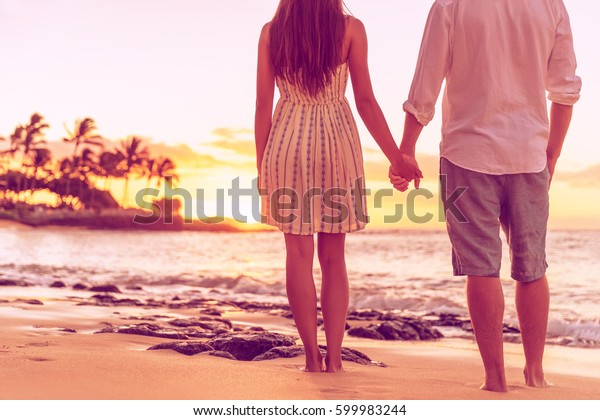 Couple from behind relaxing watching sunset on hawaiian beach together holding hands