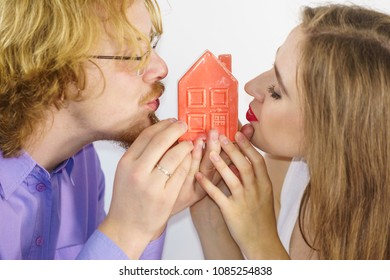 Couple being happy about new apartament. Man and woman kissing house model. New home buying, real estate concept.