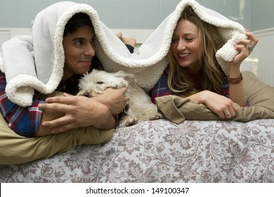 A couple being playful in the bedroom with a dog.
