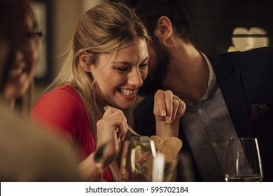 Couple are being romantic while having a meal in a restaurant. The man is kissing the woman on on the cheek and she is giggling.
