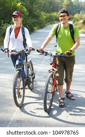 Couple  bicycler  walking with bikes from park