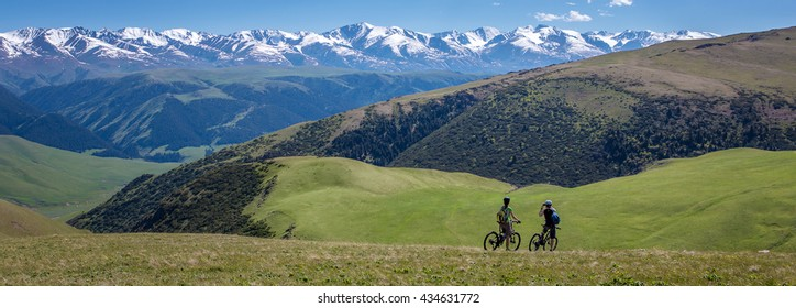 Couple of bicyclists traveling among green hills and looking at