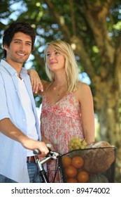 Couple with a bike and basket of produce