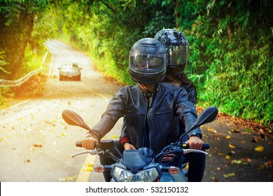 couple biker riding motorcycle on asphalt