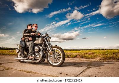Pareja motociclista con chaqueta de cuero cabalgando una motocicleta en la carretera