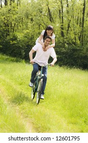 couple biking in park, laughing and hugging