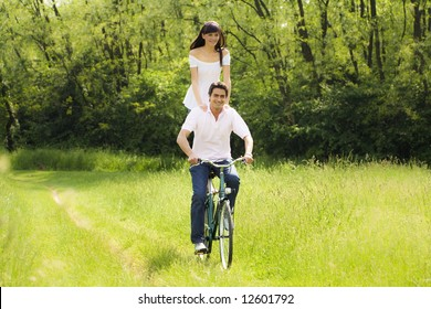 couple biking in park, smiling and hand on shoulders