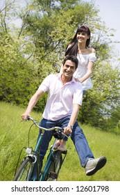 couple biking in park, smiling and hands on shoulder