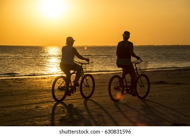 Couple biking in sunset light on Sanibel Island.