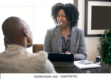 Couple of black female businesswomen or partners arguing at work or a bossy manager doing a job interview or perfomance review to an employee and looking disappointed.