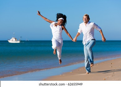Couple - black woman and Caucasian man � having a walk jumping on a beach in their vacation