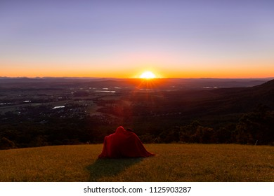 A couple with a blanket around them watching the sunset over the horizon in the Gold Coast hinterland