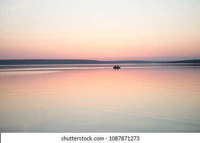 Couple in a boat in a lake or pond or river in a sunset calm water no wind summer minimalism silhouette people beautiful meditation tourism outdoor meditation life happiness