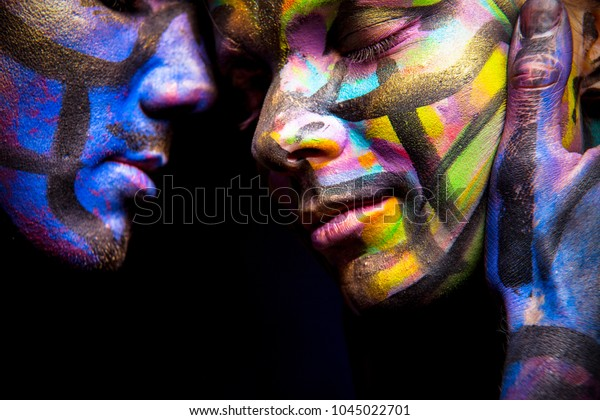 Couple in body art and face art. Painted hands and face. Love. Passion portrait.