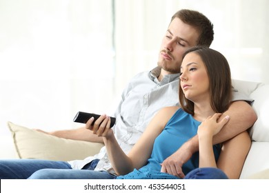 Couple bored watching tv with a the hand holding the remote control sitting on a sofa at home