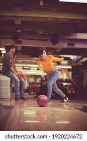 Couple in bowling alley. Woman throws a bowling ball.