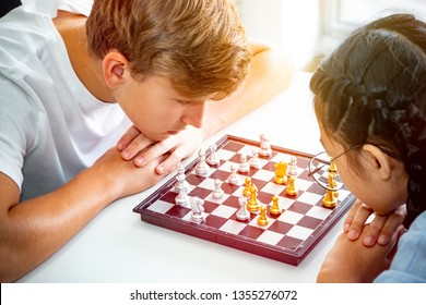 a couple boy and girl as teenage playing chess board game battle while thinking action and sitting on chair