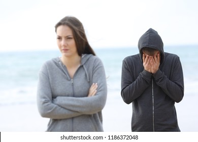 Couple break up on the beach with a girl leaving man alone