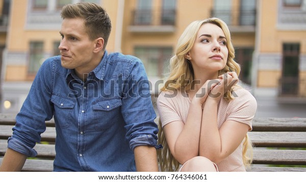 Couple breaking up, upset man and crying woman sitting on bench, divorce