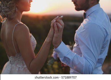 The couple, the bride and groom holding hands at sunset in the mountains