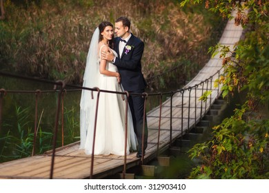 Couple of bride and groom stading on the bridge over the river