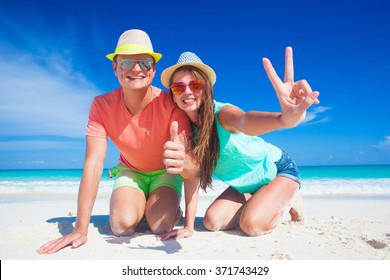 Couple in bright clothes and hats sitting at sandy tropical beach. gesture