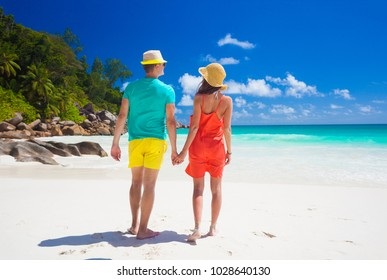 Couple in bright clothes on a tropical beach at Praslin, Seychelles.