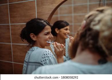 Paar, die sich die Zähne zusammen im Badezimmer zu Hause geputzt haben
