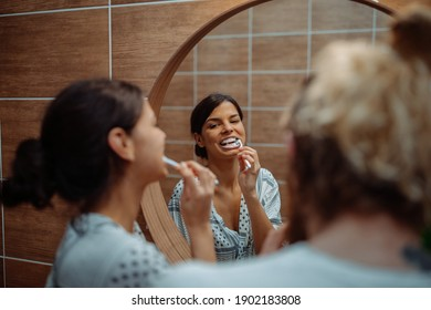 Couple brushing their teeth together in the bathroom at home
