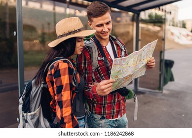 Couple at bus stop study map of city attractions