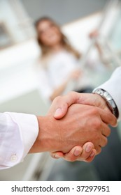 Couple of business people handshaking in an office